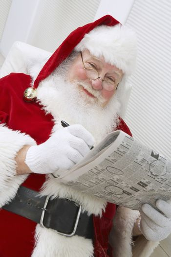 Happy Santa Clause searching for a job in a newspaper