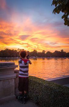 Young man shooting the sunset in Buen Retiro park