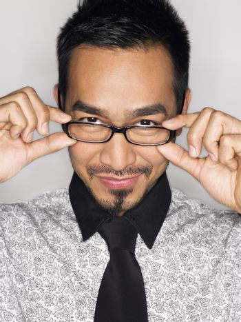 Man wearing glasses and smiling in studio portrait head and shoulders