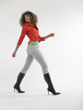 Full length of a young afro woman with curly hair walking against white background