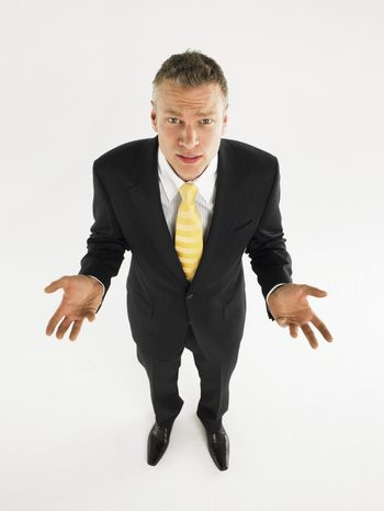 Full length portrait of a businessman making do not know sign against white background