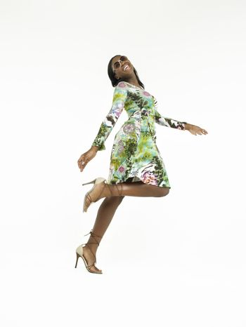 Full length of a young African American woman walking in heels against white background