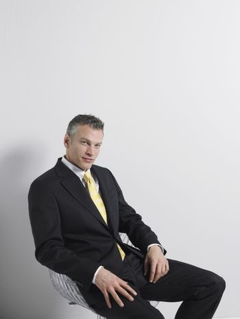Portrait of a confident businessman sitting in swivel chair against gray background