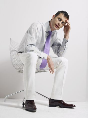 Anxious young businessman sitting in swivel chair against white background