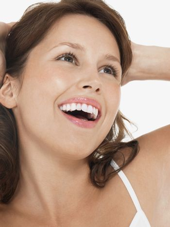 Closeup of a young brunette woman laughing as she looks up