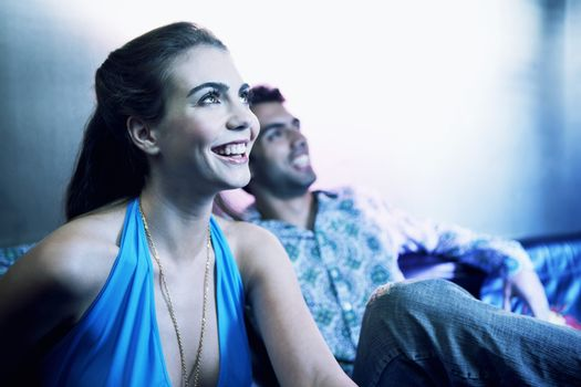 Happy young couple sitting side by side on sofa and looking Up at a bar