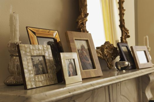 Closeup of marble fireplace mantel with framed pictures and mirror