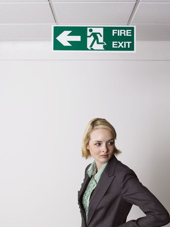 Young blonde businesswoman standing under exit sign in office