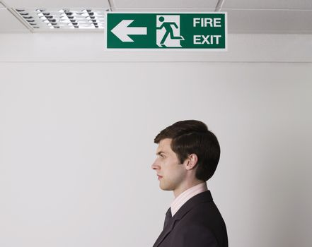 Side view of a young businessman standing under exit sign