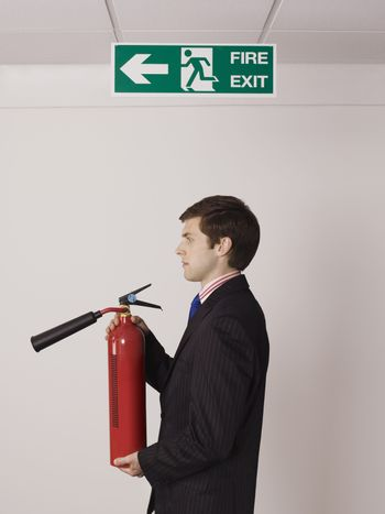 Side view of a young businessman holding fire extinguisher under exit sign