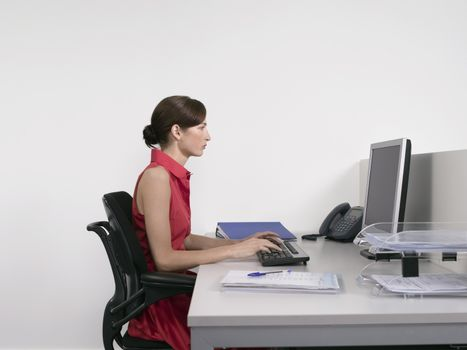 Side view of a female office worker using computer at desk in office