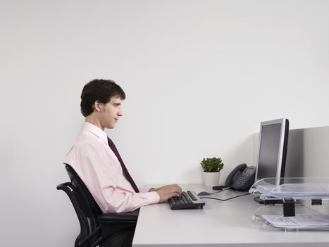 Side view of a male office worker using computer at desk in the office