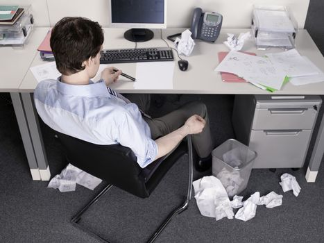 Rear view of a businessman brainstorming at office desk