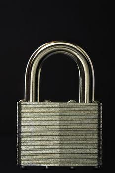 Close-up of padlock against black background