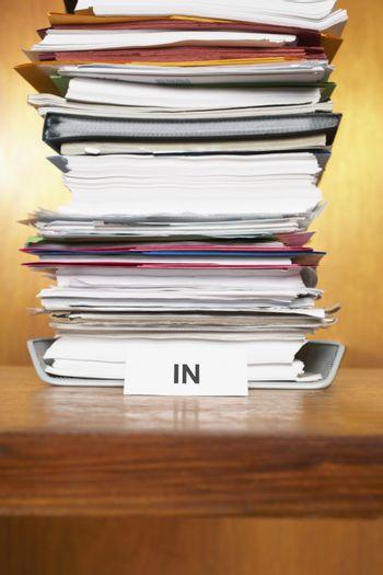 Inbox with stack of paperwork on desk