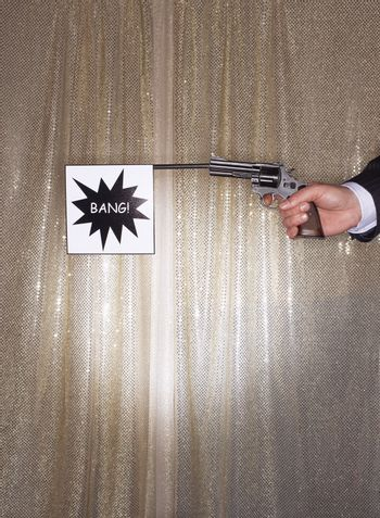 Hand of a businessman holding pistol with bang flag