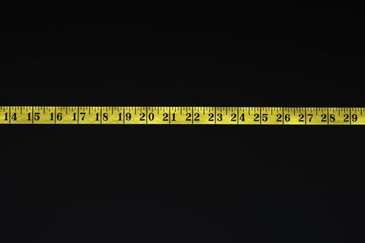 Measuring tape over black background