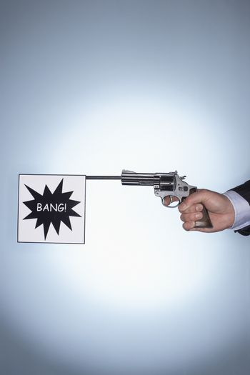 Hand of a businessman holding pistol with bang flag against colored background