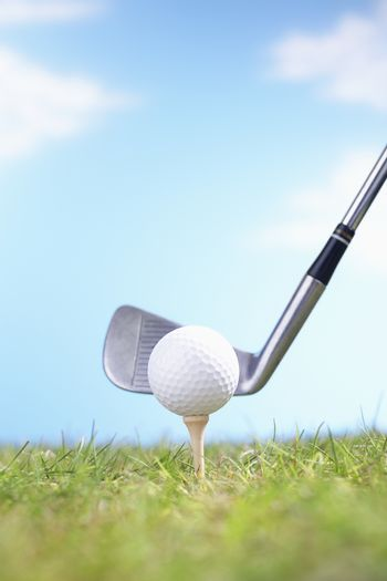 Golf ball on tee with driver ready to tee off