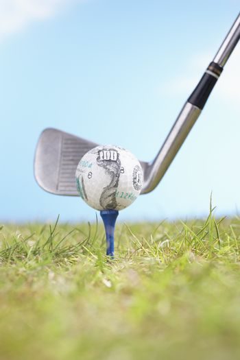 Golf ball with hundred dollar logo on tee with driver ready to tee off