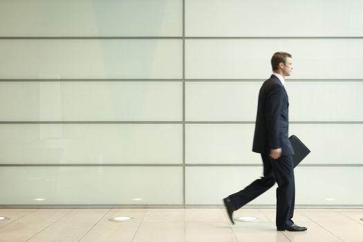 Side view of young businessman walking in passage of office