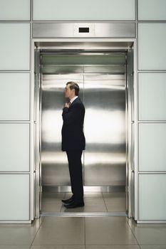 Profile shot of middle aged businessman adjusting necktie in elevator preparing for interview