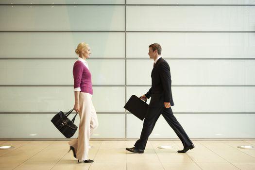 Profile shot of businesspeople with handbags walking in office corridor