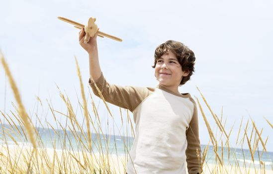 Boy Flying Toy Airplane Among Plants On Beach