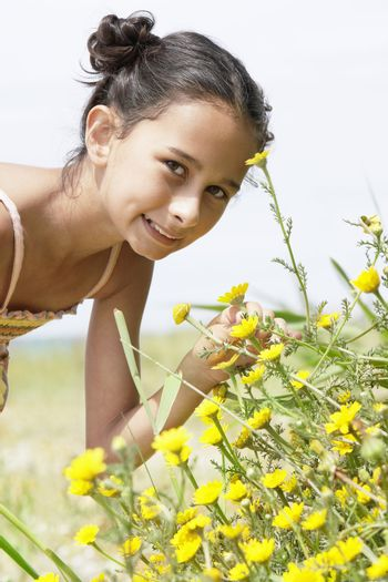 Portrait of a cute preadolescent girl bending down to smell flower in field