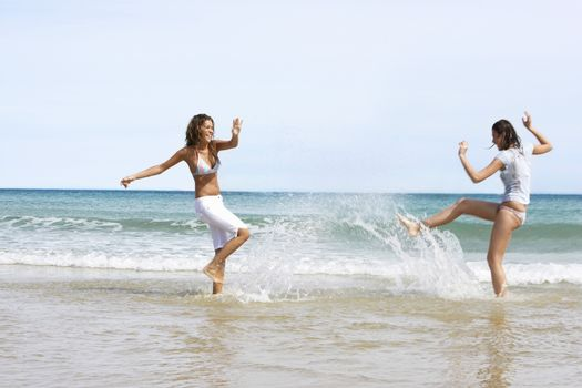 Two Young Women Splashing Each Other on Beach