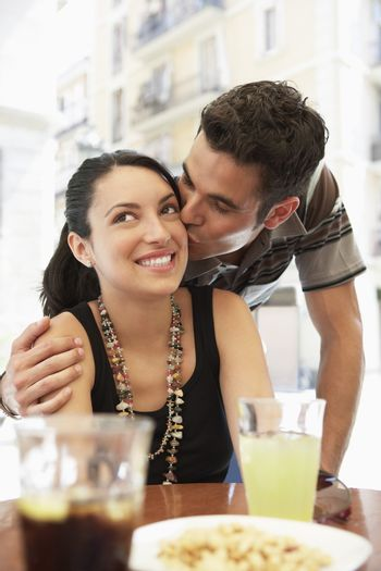 Young man kissing in woman's cheek while sitting at sidewalk cafe