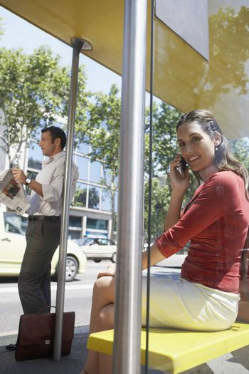 Portrait of a woman on a call while man waiting for a bus at bus stop