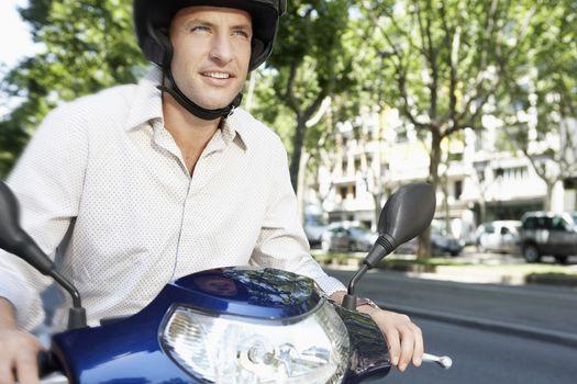 Businessman riding motor scooter along city street