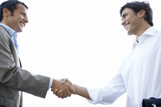 Businessmen shaking hands side view