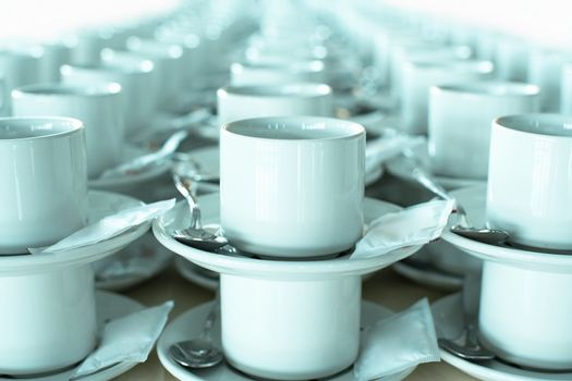 Rows of stacked teacups and saucers close-up.
