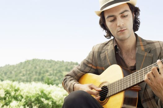 Handsome young man playing acoustic guitar outdoors