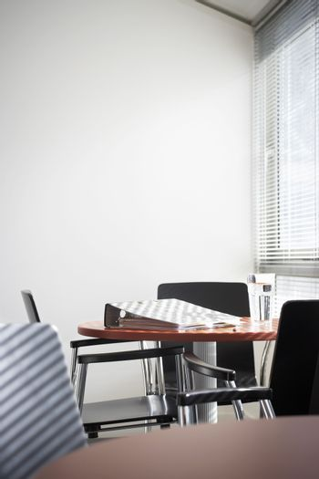 Empty office with binder and water glass on table