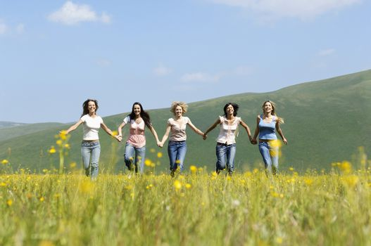 Group of happy multiethnic female friends running against mountain range