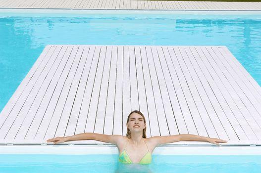 Teenage girl with eyes closed sunbathing at poolside