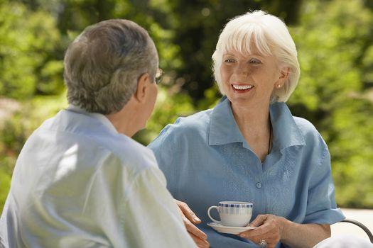 Happy senior woman conversing with husband in backyard