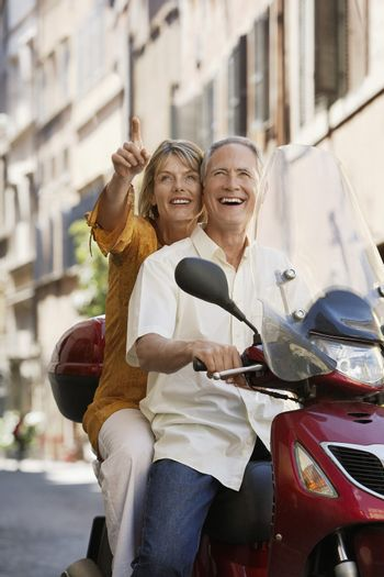 Middle-aged couple sightseeing on scooter in Rome Italy
