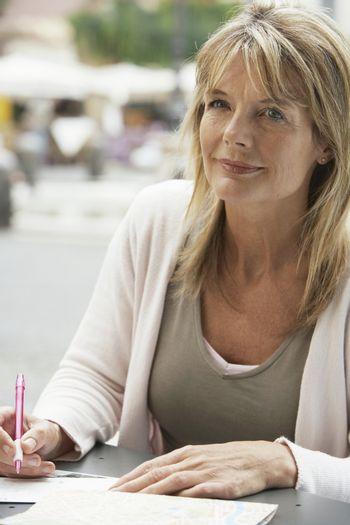 Thought middle aged woman writing letter at outdoors cafe