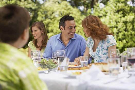 Happy parents looking at each other while having lunch with family in backyard