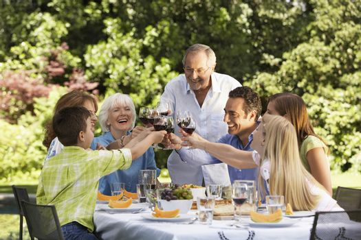 Family toasting at lunch table in back yard