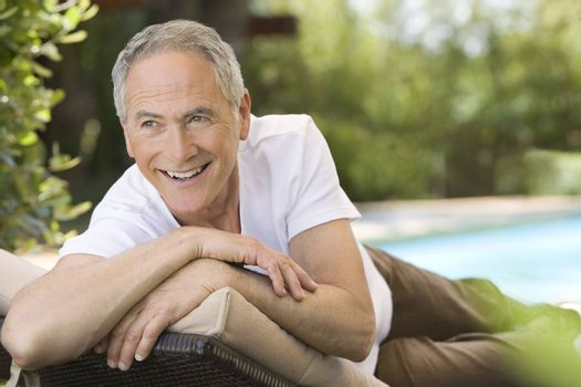 Middle-aged man reclining on deck chair in garden