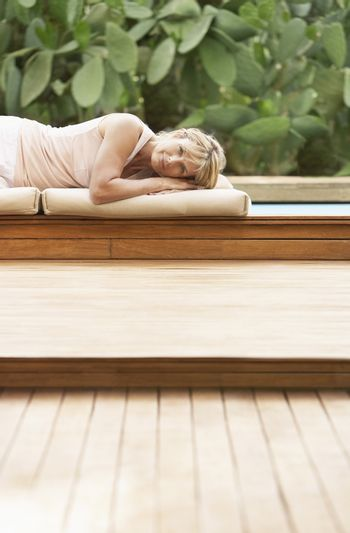 Portrait of middle aged woman lying on cushions by swimming pool