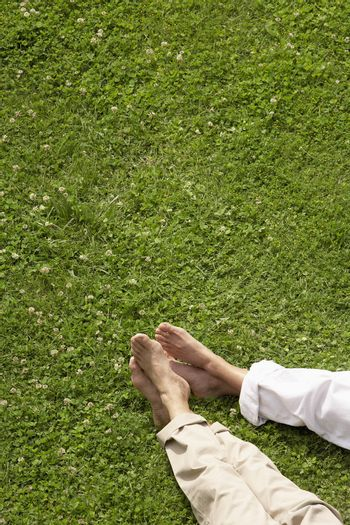 Low section of couple relaxing on grass