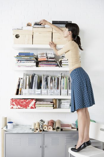 Businesswoman reaching for Shelf in home office
