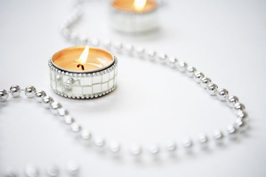 Closeup of lit tealight candles and silver garland