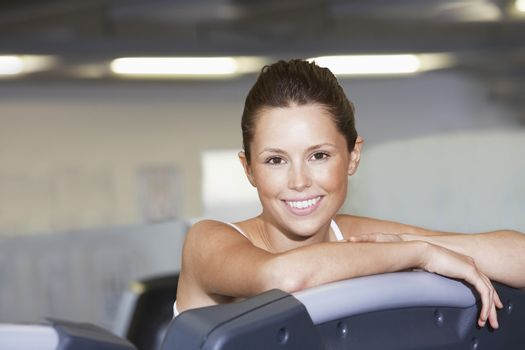 Young Woman resting on treadmill at Health Club portrait